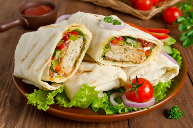 Turkish doner kebab shawarma roll with meat vegetables and pita bread on a wooden Premium Photo