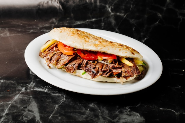 Turkish doner in tandir bread inside white plate. Free Photo