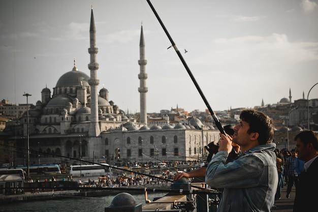 Turkish fishermen with rod on the galata bridge. Premium Photo