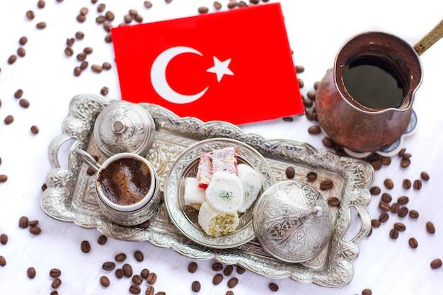 Turkish flag next to traditional turkish coffee, sweets and jezve Premium Photo