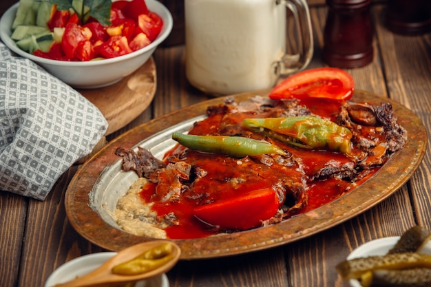 Turkish iskender doner in copper plate wirh tomato sauce and green pepper. Free Photo