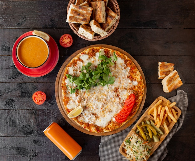 Turkish lahmajun with cheese, served with lemon, parsley with tomato soup Free Photo