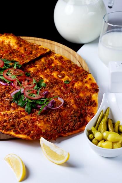 Турецкая пицца lahmajun, украшенная кольцами томатного лука и петрушкой Бесплатные Фотографии