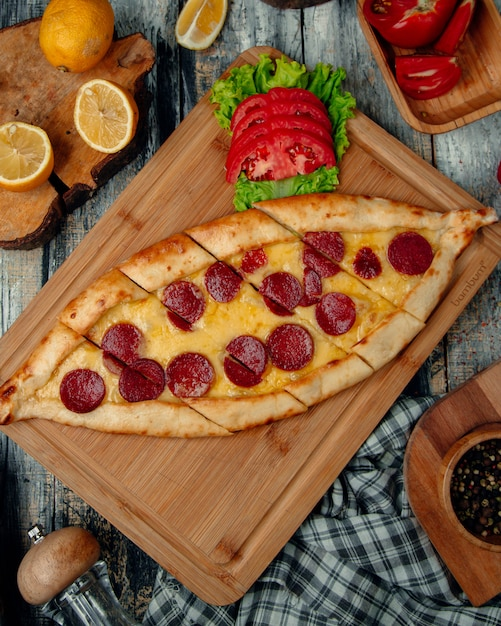 Turkish pizza pide with pepperoni , tomato and herbs. Free Photo