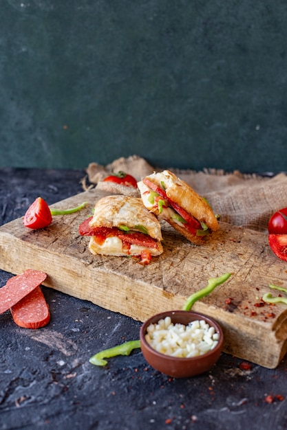 Turkish sausage sandwich cut into pieces on a wooden board Free Photo