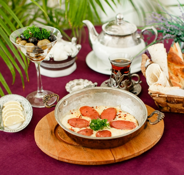 Turkish sausage with eggs in steel pan, teapot, olives and bread Free Photo