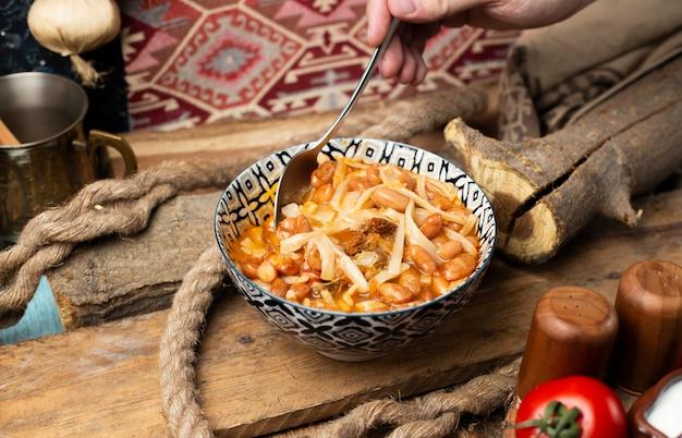 Turkish soup kuru fasulye with herbs and spices. Free Photo