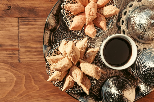 Turkish sweets with coffee on a wooden table Premium Photo