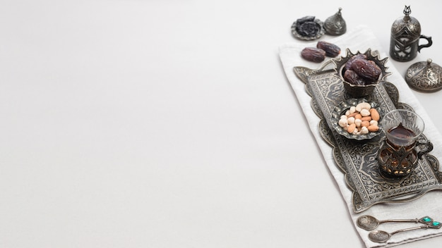 Turkish tea in glass and date fruits for dessert on oriental tray isolated over white background Free Photo