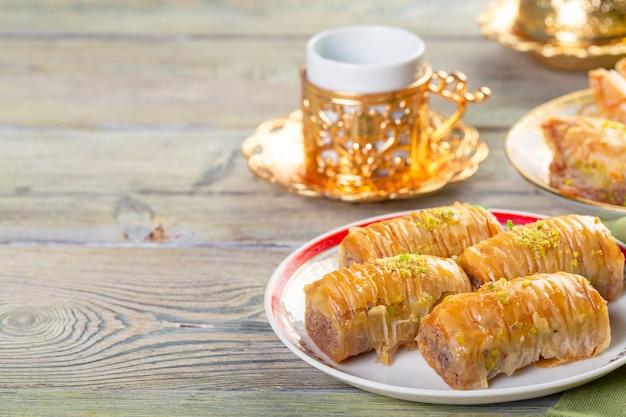 Turkish traditional dessert baklava with tea on dark. fresh and healthy dessert. Premium Photo
