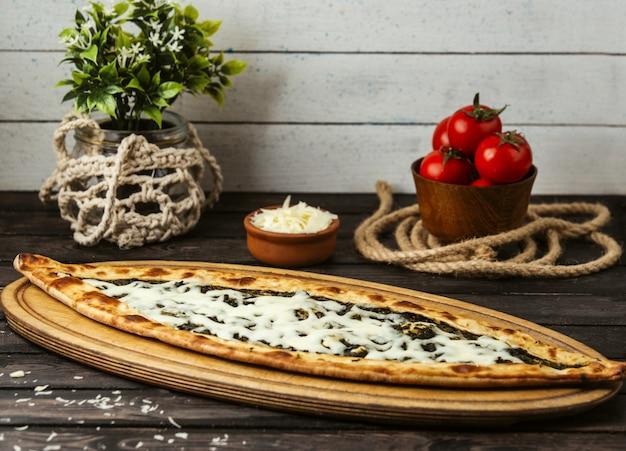 Турецкий традиционный пиде с сыром и зеленью на деревянной доске Бесплатные Фотографии