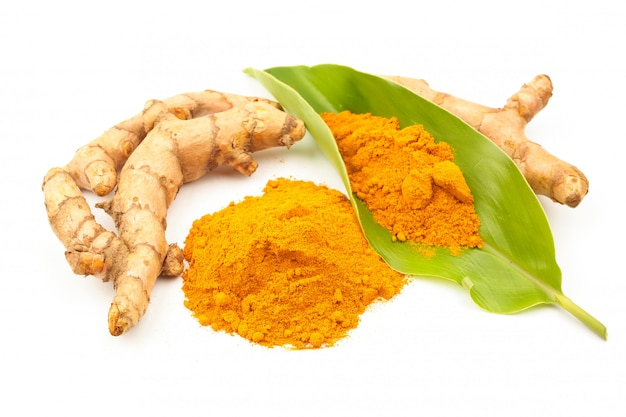 Turmeric powder and fresh turmeric (curcuma) with green leaf on white background. herbal Premium Photo