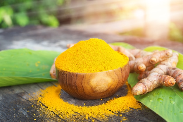 Turmeric powder and fresh turmeric in wooden bowls on old wooden table Premium Photo