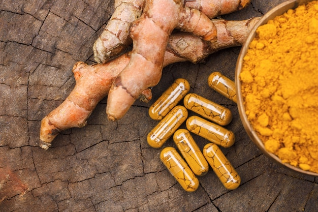 Turmeric powder in wooden bowls and turmeric capsules on wooden background Premium Photo
