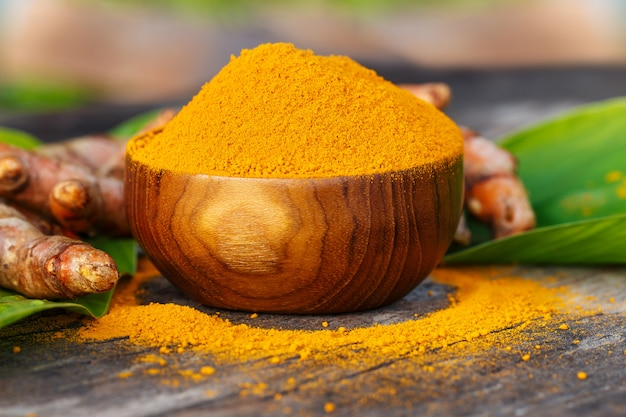Turmeric powder in wooden bowls on wooden table Premium Photo