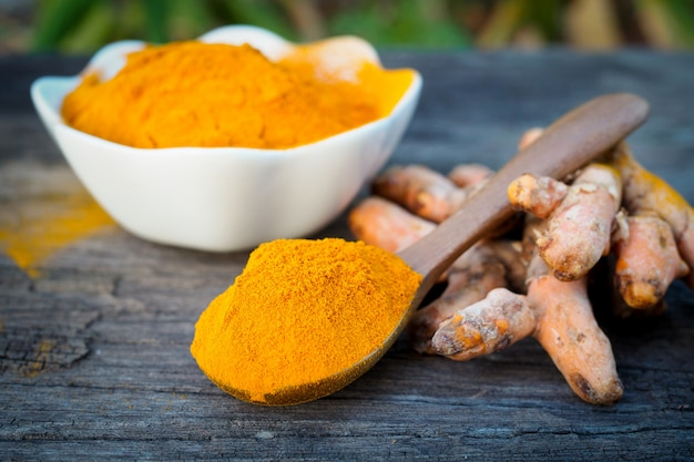 Turmeric powder in wooden spoon on old wooden table. herbal Premium Photo