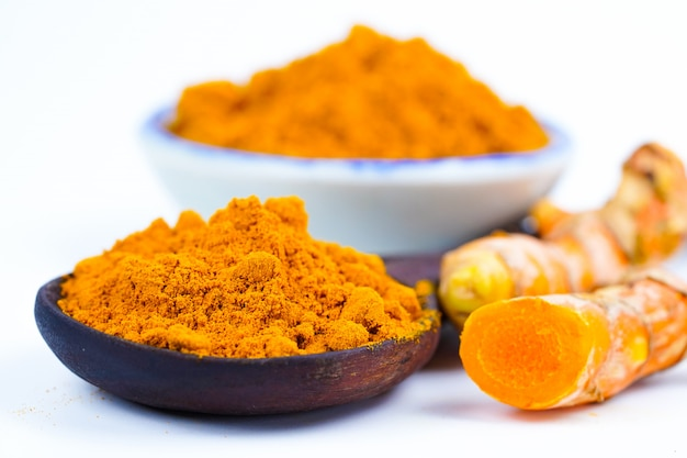 Turmeric roots and powder herb on wooden background. Premium Photo