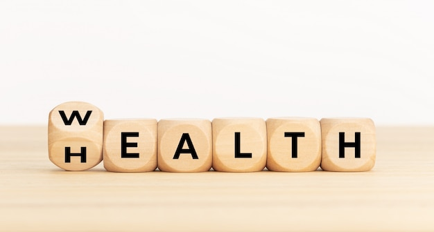 Turning wooden dice with word wealth to health Premium Photo
