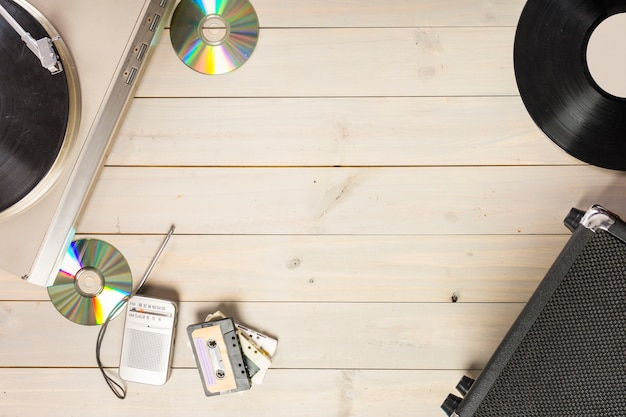 Turntable vinyl record player; compact disc; cassette tape and radio on wooden table Free Photo