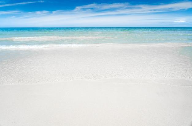 Бирюзово-синее море с белым песком и солнечным небом Premium Фотографии
