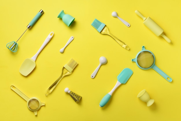 Turquoise cooking utensils on yellow background. food ingredients. Premium Photo