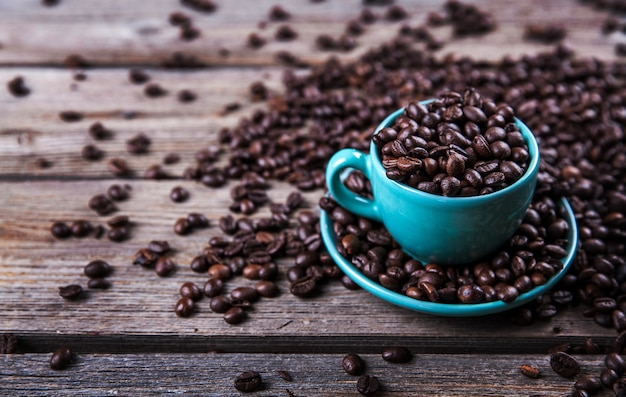 Turquoise cup with coffee beans on a wooden. Premium Photo