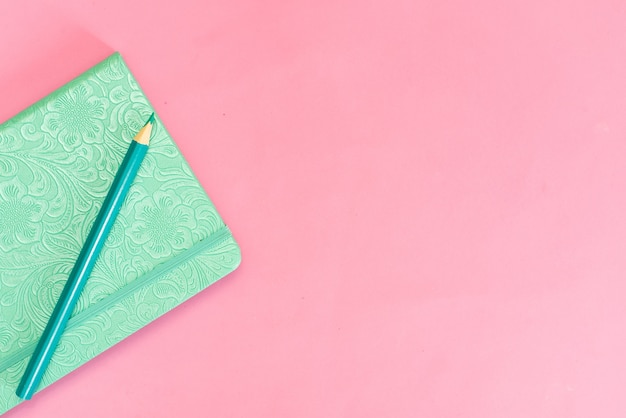 Turquoise notebook on a pink background and pencil Premium Photo