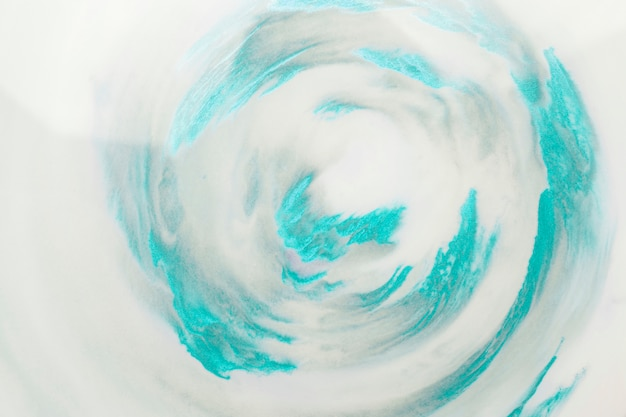 Turquoise paint strokes in swirl pattern over white surface Free Photo