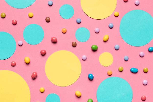 Turquoise and yellow circular frames with colorful candies on pink background Free Photo