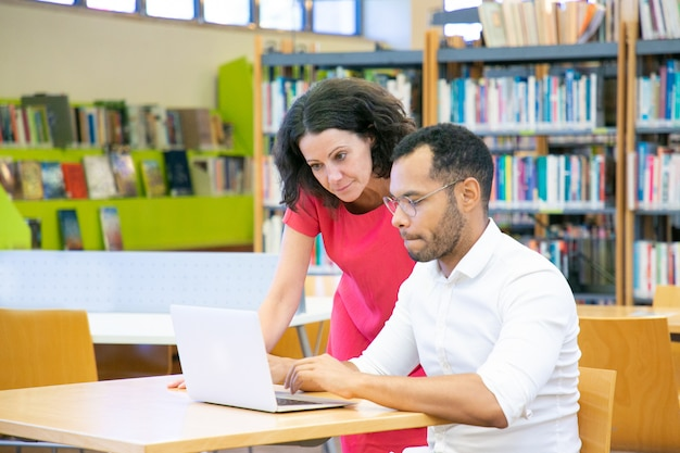 Tutor helping student with research in library Free Photo
