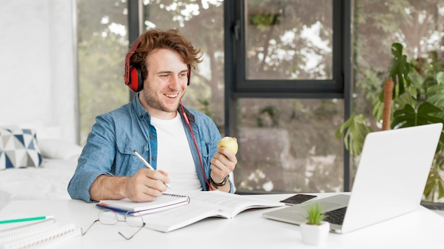 Tutor at home holding an apple and smiles Free Photo