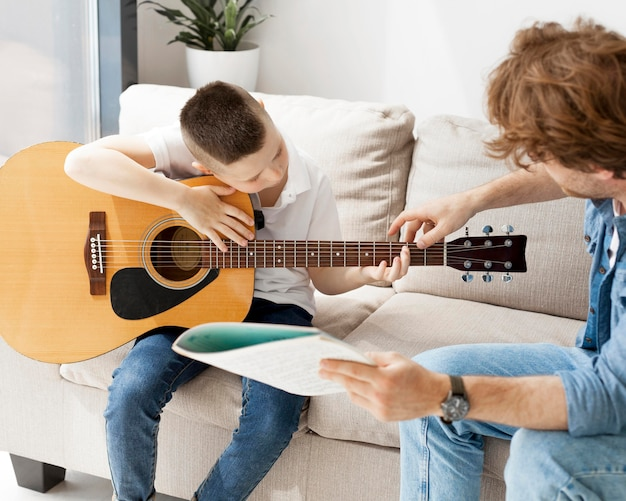 Tutor showing his student how to hold hand on guitar Free Photo