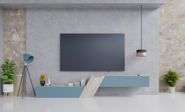 Tv on blue cabinet design in modern living room with lamp, flower and plant on cement wall. Premium Photo