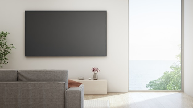 Tv on white wall against sofa in home or villa. Premium Photo