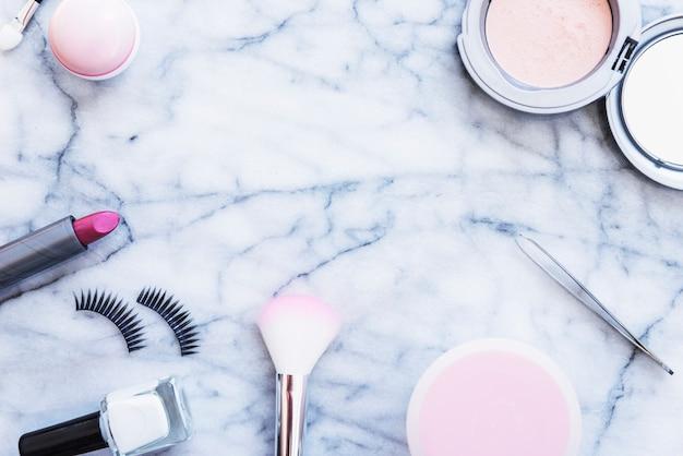 Tweezers; blushes; nail varnish; lipstick; compact powder and eyelashes on marble textured background Free Photo