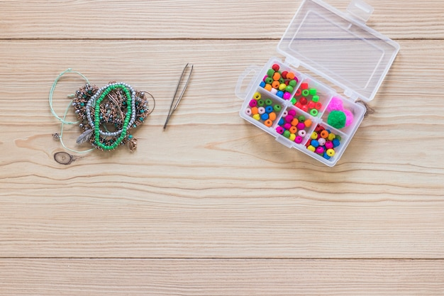 Tweezers; bracelet and beads in the white plastic box on wooden table Free Photo
