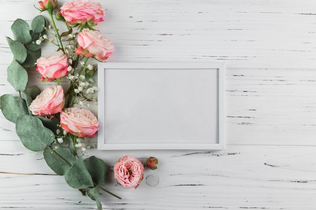 Twig; roses and baby's breath flowers near the white blank frame on wooden textured surface Free Photo