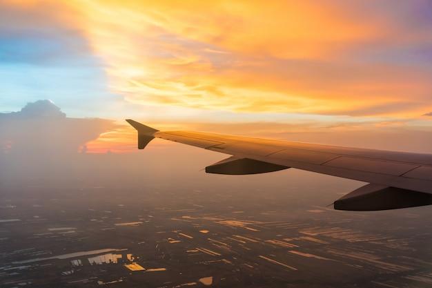 Заход солнца в twilight времени с крылом самолета и неба облака. фото применено для туроператоров. Premium Фотографии