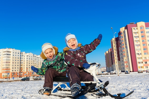 Twin brothers posing on snow scooter Premium Photo