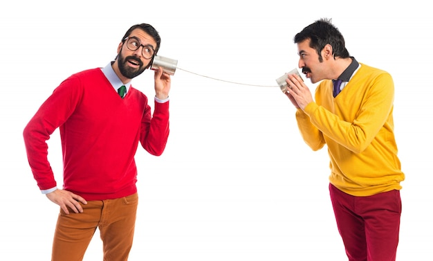 Twin brothers talking through a tin phone Free Photo