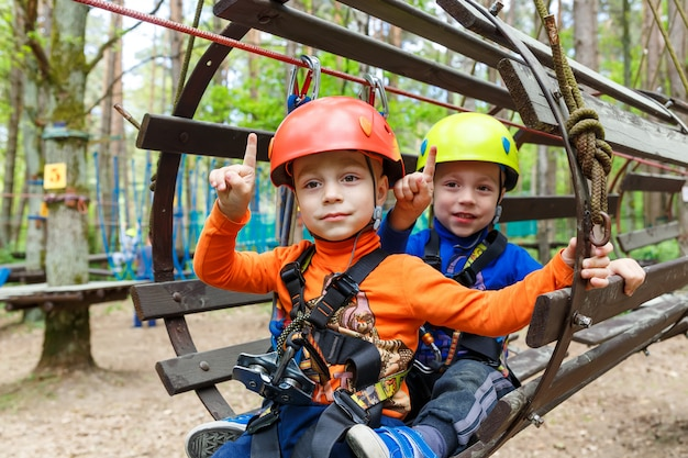 Twin brothers wearing helmet and climbing Premium Photo