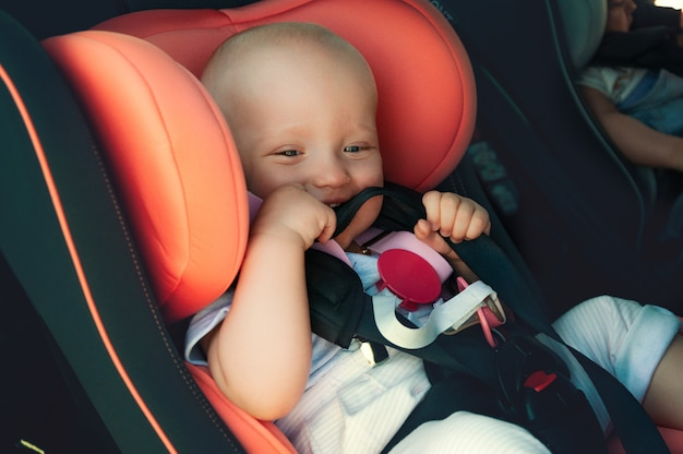 Twins boy and girl in child seats in the car. safety transportation for babies. children up to a year. Premium Photo