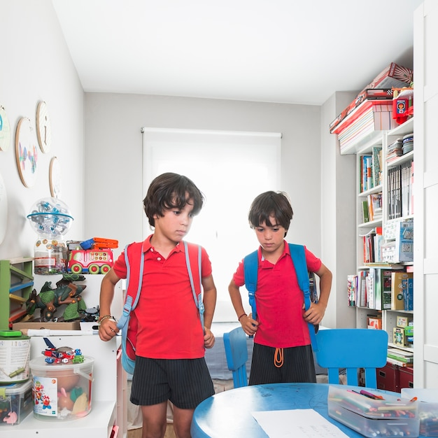 Twins with backpacks standing in preschool room Free Photo