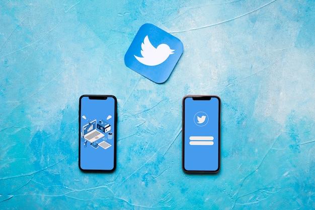 Значок приложения twitter и два телефона на синей окрашенной стене Premium Фотографии
