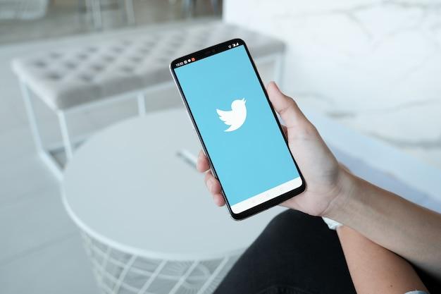 Женщин, занимающих смартфон с логотипом twitter на экране. twitter - это онлайн-сервис для социальных сетей для микроблогов и сетевого общения. Premium Фотографии