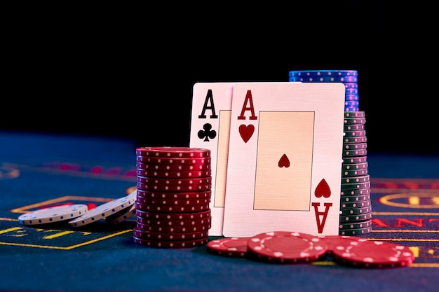 Two aces standing leaning on chips piles Premium Photo