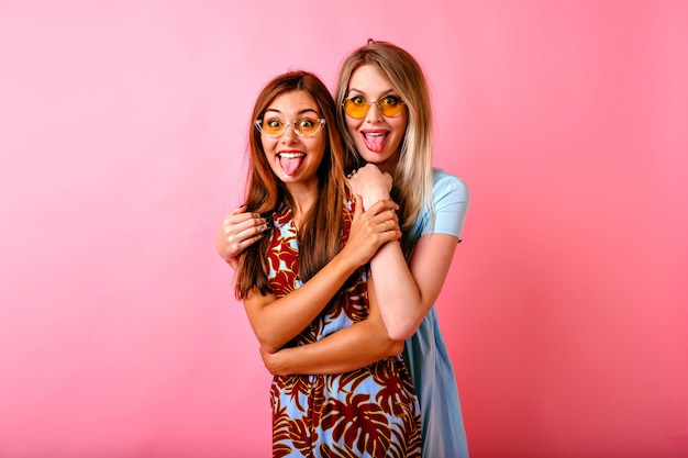 Two adorable happy young women having fun together showing tongues Free Photo