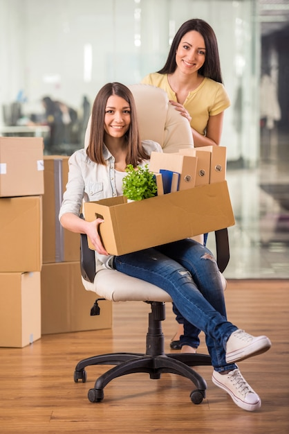 Two adult businesswomen moving into a new office. Premium Photo