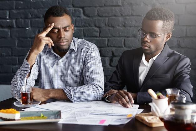 Due uomini d'affari afro-americani che firmano il contratto durante la riunione d'affari alla scrivania Foto Gratuite