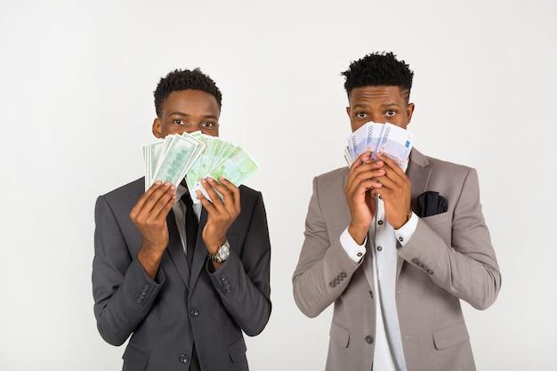 Два африканца в костюмах с деньгами в евро Premium Фотографии